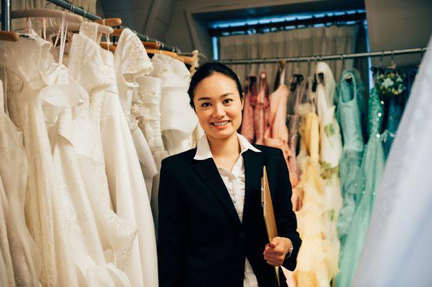 美しいドレスに囲まれて仕事をするドレスコーディネーター
