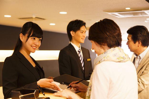 ホテルフロントのバイトをする女性